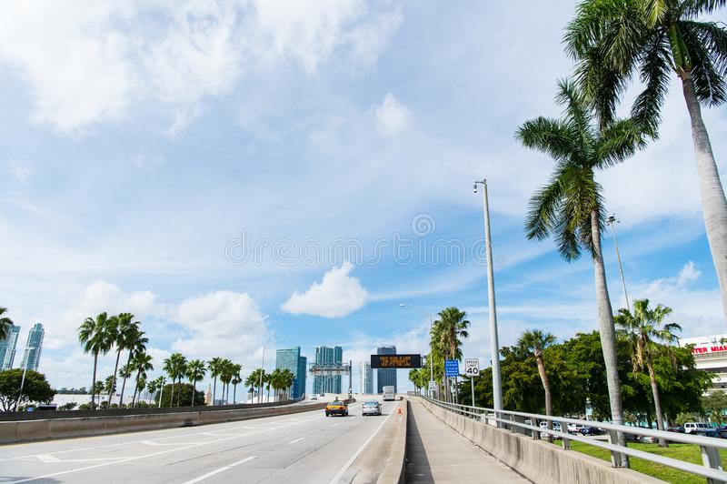 Highway or roadway with cars and skyline of miami, usa. Road with traffic signs for transport vehicles and palm trees on cloudy bl royalty free stock image