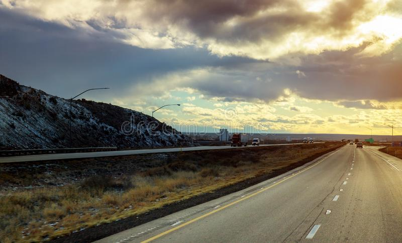 A highway runs from New Mexico through the brush and mesas of the high desert. New Mexico view panoramic a highway runs from through the brush and mesas of the stock image