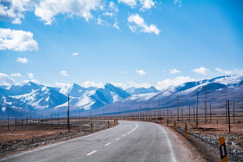 Highway by the snow mountain in high altitude region stock photography