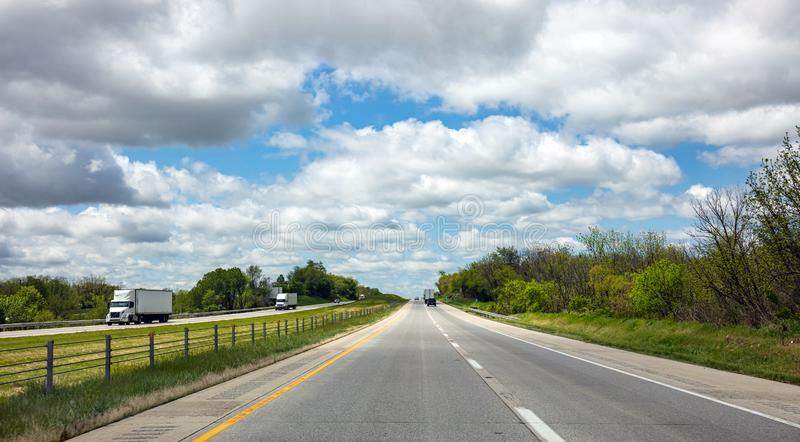 Long highway in the american countryside, blue cloudy sky background stock images