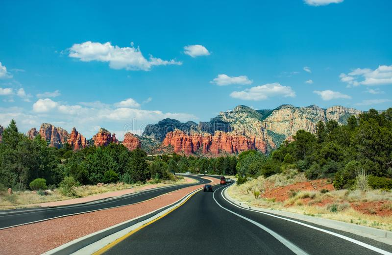 Highway to beautiful red mountains in Sedona. Arizona,USA. Blue sky with clouds in the background. Copy space royalty free stock photo