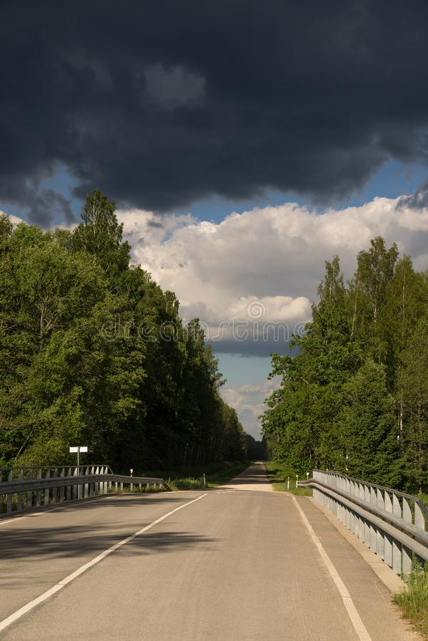 Highway to hell. Car road, bridge and clouds of storm, natural environment background. stock photography
