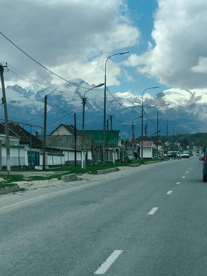 Highway to the left of the house and mountains as well as the sky with white clouds.  stock photography