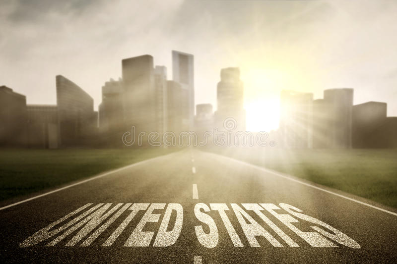 Highway with United States word at sunrise. Asphalt highway towards to a town with sunrise and United States word royalty free stock photo