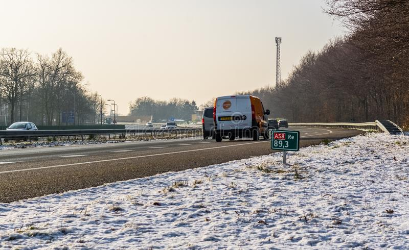 The A58 highway in winter season with cars passing by, Roosendaal, The netherlands, 23 january, 2019. A58 highway in winter season with cars passing by stock image