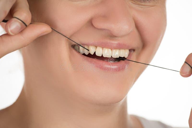 Higiena oralny zagłębienie Młoda dziewczyna czyści zęby z floss, zdjęcie stock