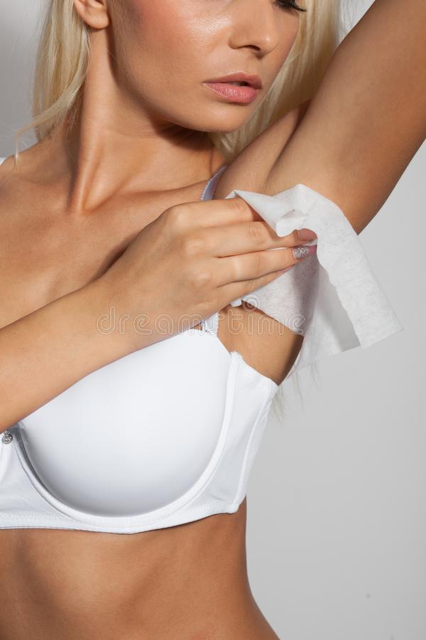 Woman use wet wipes to clean armpit royalty free stock image