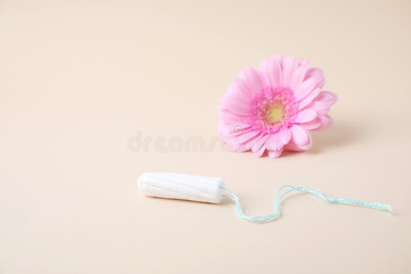 Higieniczny tampon i kwiat na beżowym tle zdjęcie royalty free