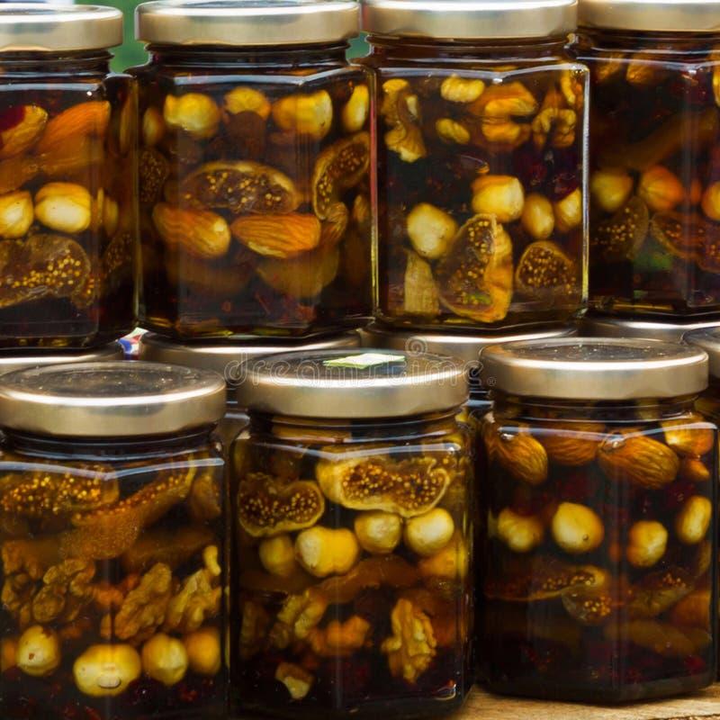 Higos con la miel, la almendra y las avellanas colocándose en el contador, M fotografía de archivo