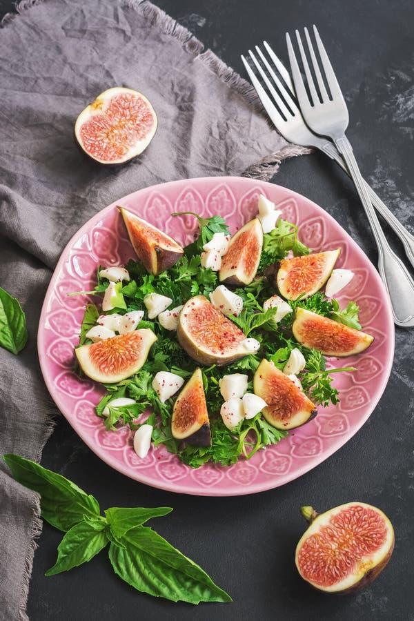 Higos, queso y verdes frescos Ensalada vegetariana sana en un fondo concreto Visión de arriba, superior, endecha plana fotografía de archivo libre de regalías