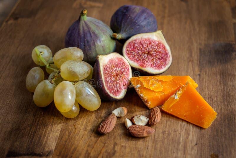 Higos uvas, almendras y queso duro en una tabla imagen de archivo