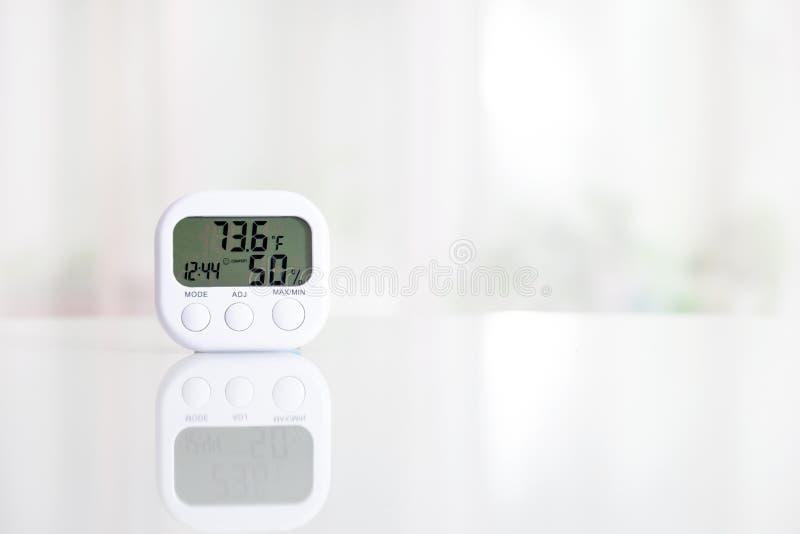 Higr?metro electr?nico blanco en la tabla blanca delante de la ventana Modo de Fahrenheit fotos de archivo libres de regalías