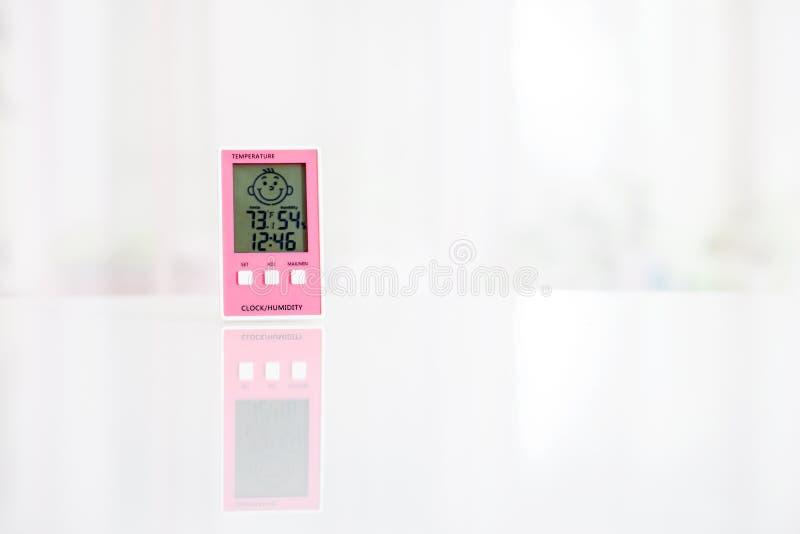 Higr?metro electr?nico rosado en la tabla blanca delante de la ventana Modo de Fahrenheit imagenes de archivo