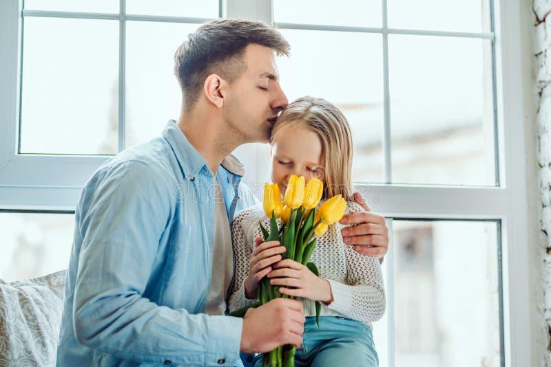 Hij is de beste papa! Dochter en vaderzitting samen op de vensterbank thuis Weinig boeket van de jong geitjeholding van tulpen royalty-vrije stock foto