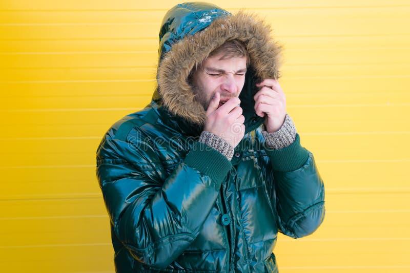 Hij heeft koud en griep Toevallige manierlaag voor koude de wintervoorwaarden Knappe mens die faux bontkap dragen modieus royalty-vrije stock foto