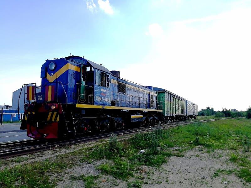 Hij locomotief is blauw met twee behandelde wagens op de spoorweg Juiste mening stock fotografie