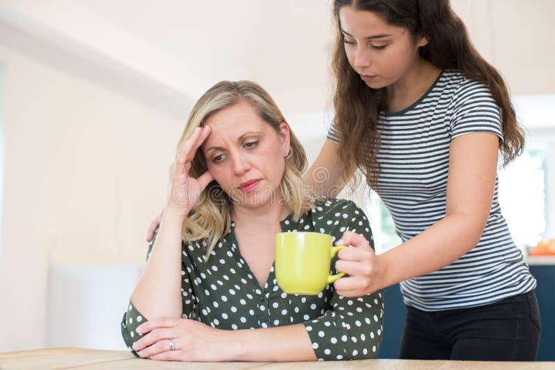 Hija adolescente que hace la bebida para el padre que sufre con H mental imagen de archivo libre de regalías