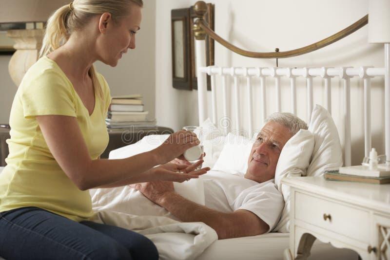 Hija adulta que da la medicación mayor del padre masculino en cama en casa imagen de archivo