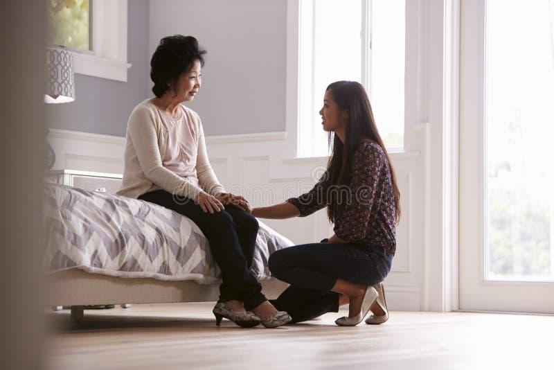 Hija adulta que habla con la madre deprimida en casa imagen de archivo