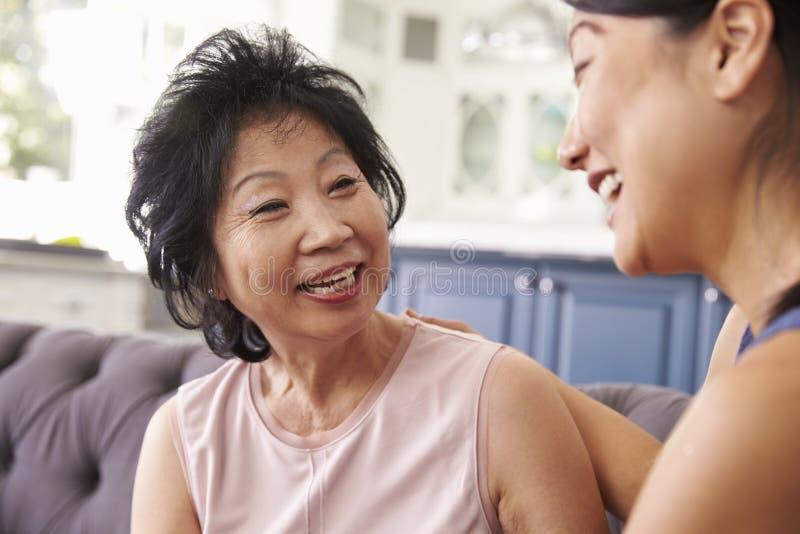Hija adulta que habla para mimar en casa imagen de archivo