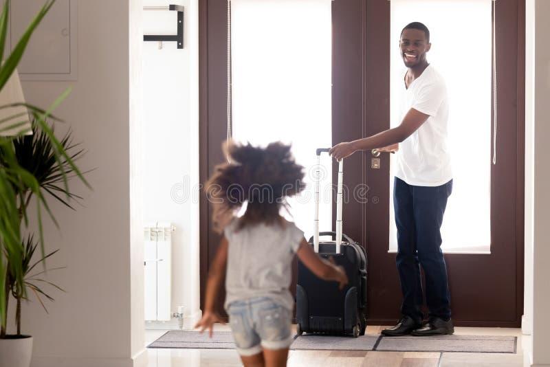 Hija africana que corre para encontrar al padre vuelto de viaje de negocios foto de archivo libre de regalías