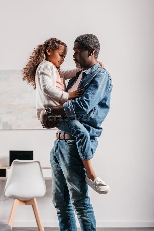 hija afroamericana de la tenencia del hombre foto de archivo