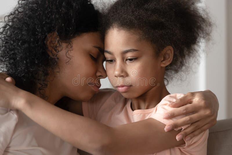 Hija afroamericana pensativa del niño que abraza la vinculación de la mamá que abraza fotografía de archivo