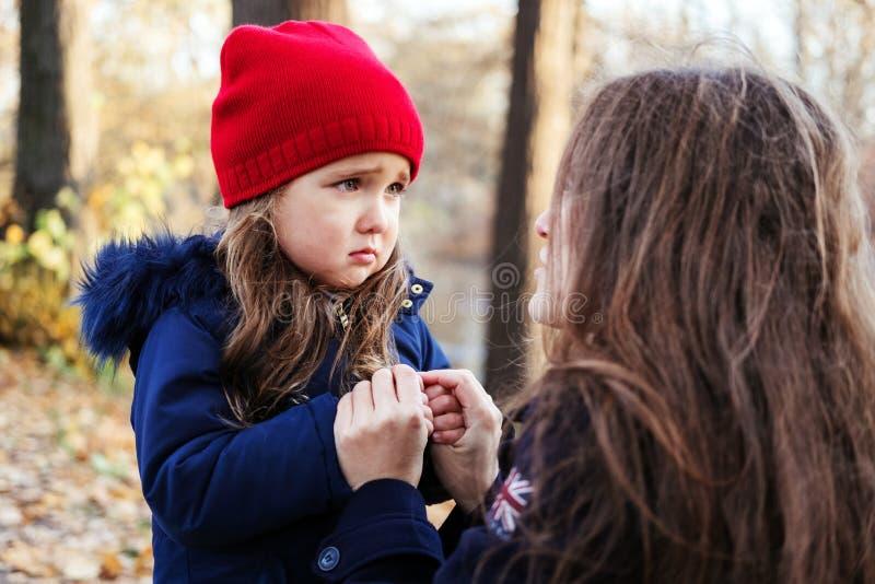 Hija asustada que lleva a cabo las manos de la madre en parque del otoño imagen de archivo
