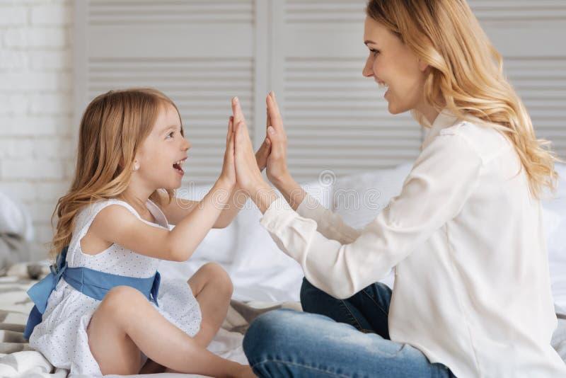 Hija bastante pequeña que da altos diez a su madre imagen de archivo libre de regalías