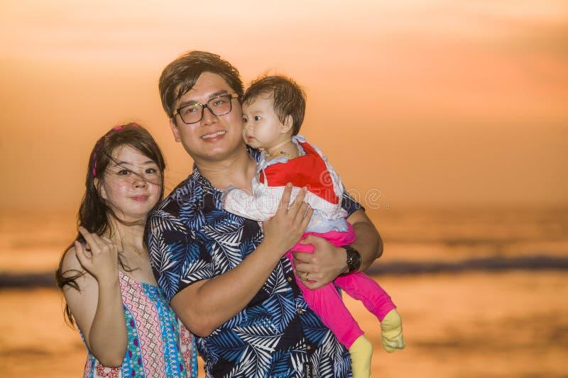 Hija china asiática feliz y hermosa joven del bebé de la tenencia de la pareja que camina en la playa de la puesta del sol que go fotografía de archivo libre de regalías