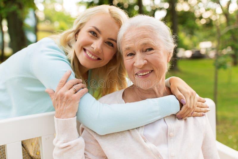 Hija con la madre mayor que abraza en banco de parque imagenes de archivo