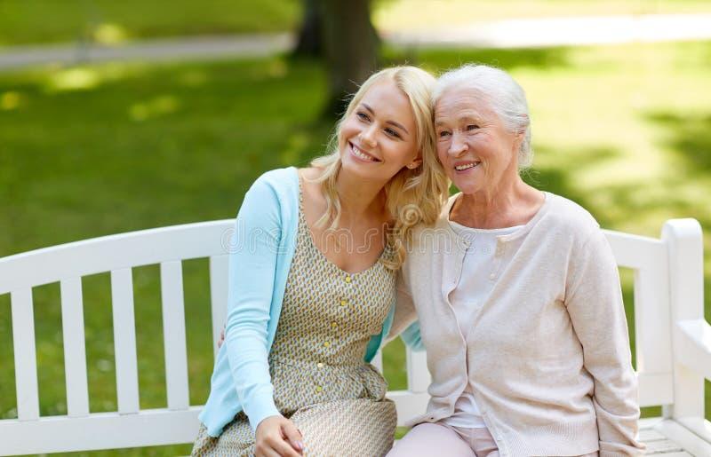 Hija con la madre mayor que abraza en banco de parque imagen de archivo libre de regalías