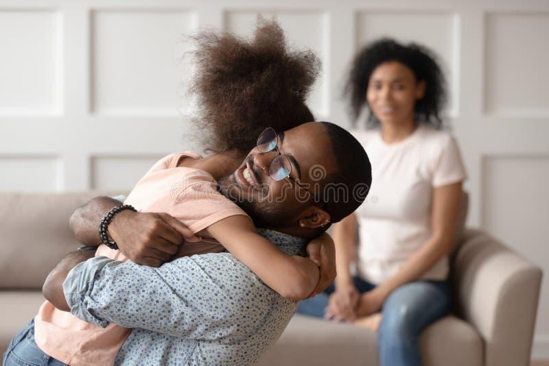 Hija de abarcamiento del papá afroamericano feliz que abraza en casa imagenes de archivo
