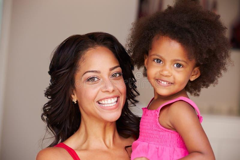 Hija de abrazo de la madre en casa foto de archivo libre de regalías