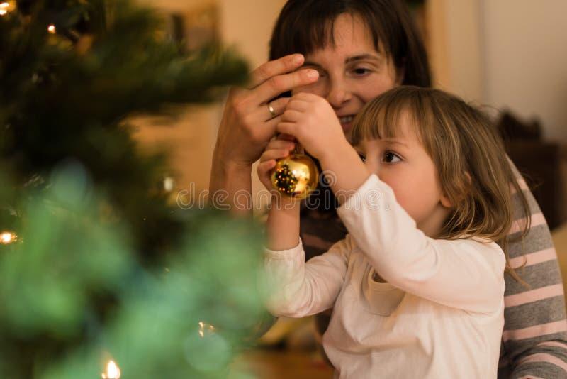 Hija de ayuda de la madre para adornar el árbol de Navidad fotografía de archivo libre de regalías