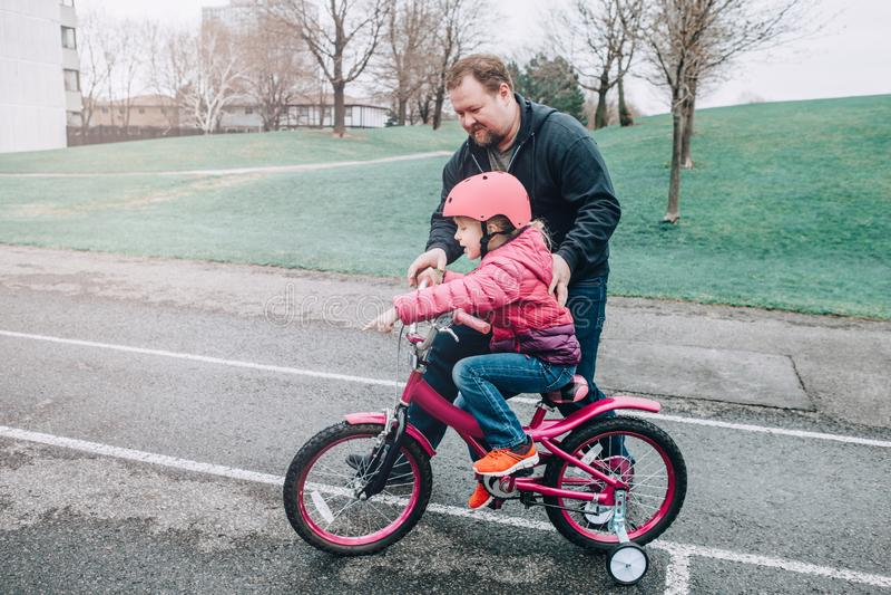 Hija de ayuda de la muchacha del padre del entrenamiento cauc?sico del pap? para montar la bicicleta imagen de archivo