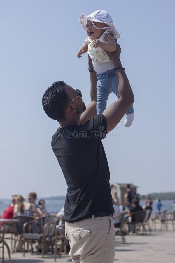 Hija de elevación del padre joven con el sombrero para arriba en el aire en un verano fotografía de archivo libre de regalías
