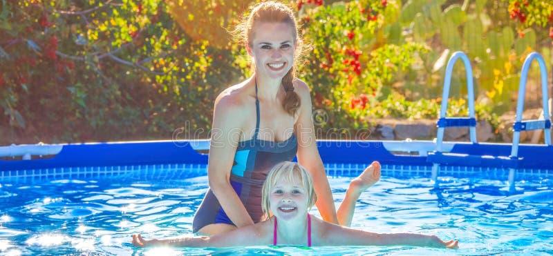 Hija de enseñanza de la madre activa feliz a nadar en piscina fotos de archivo