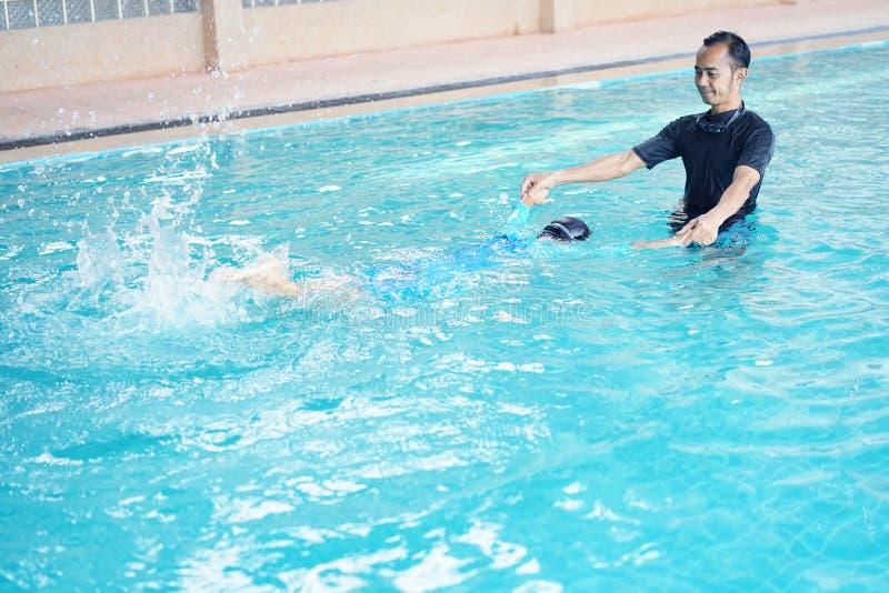 Hija de enseñanza del padre a nadar imagenes de archivo