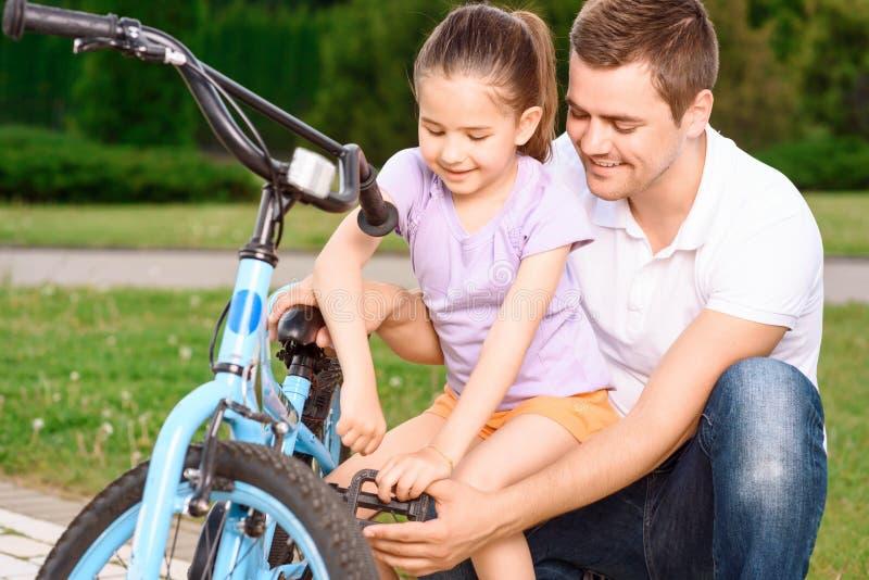 Hija de enseñanza del padre para montar una bici fotografía de archivo