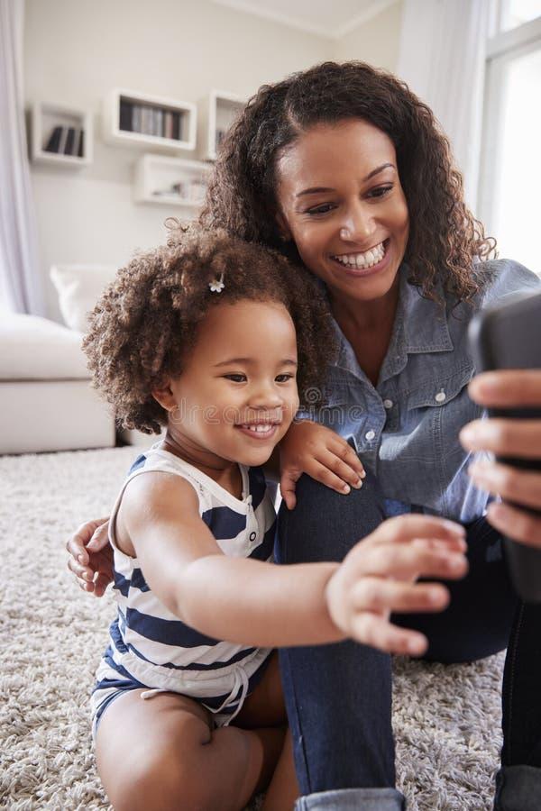 Hija de la madre y del niño que mira las fotos en smartphone foto de archivo libre de regalías