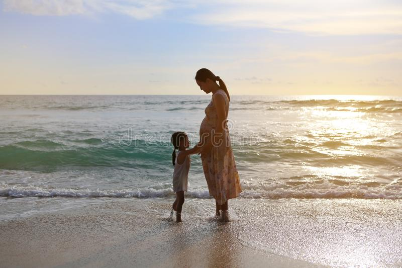Hija de la silueta que toca el vientre de la madre embarazada y que se relaja en la playa en la puesta del sol foto de archivo libre de regalías