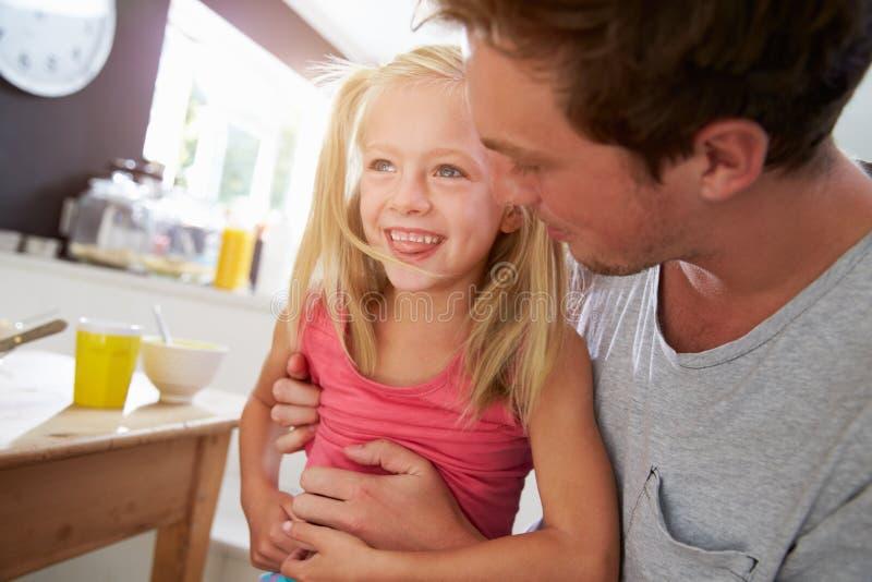 Hija de Sitting With Laughing del padre en la mesa de desayuno foto de archivo libre de regalías