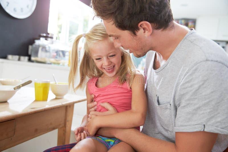 Hija de Sitting With Laughing del padre en la mesa de desayuno imagen de archivo libre de regalías