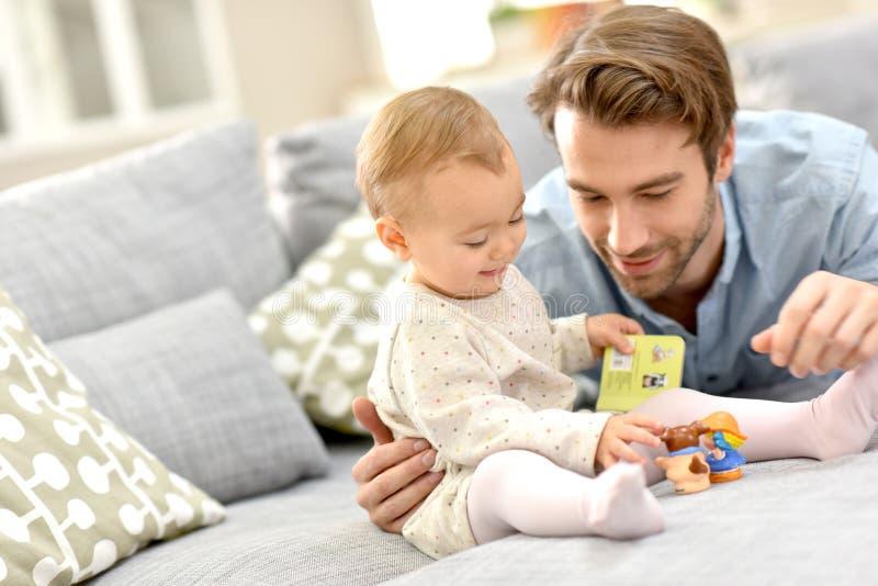 Hija del padre y del bebé que juega junto foto de archivo