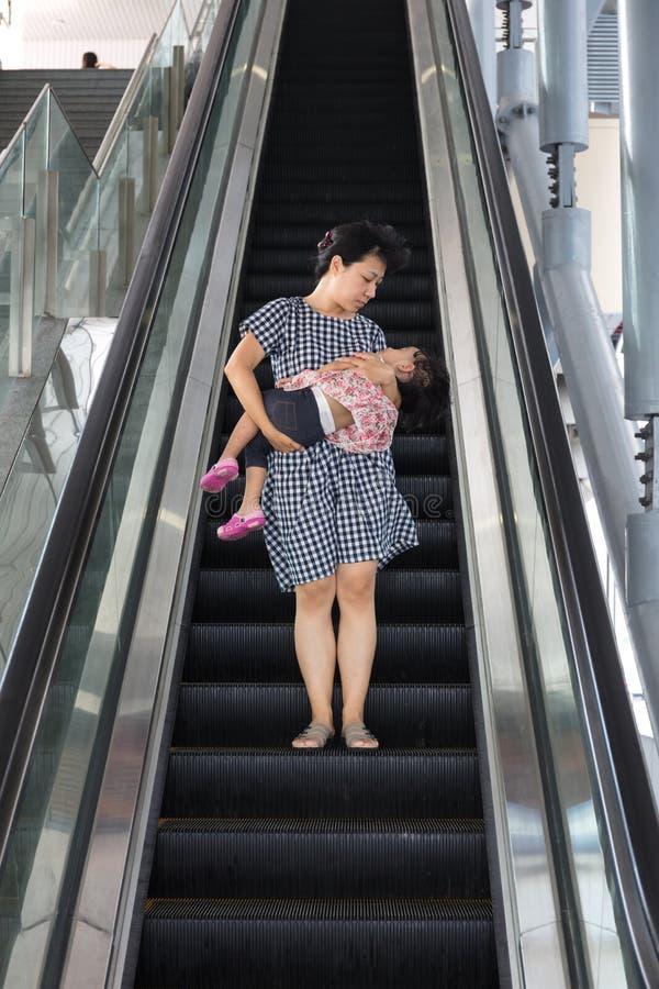 Hija durmiente que lleva de la madre china asiática que toma la escalera móvil imagen de archivo