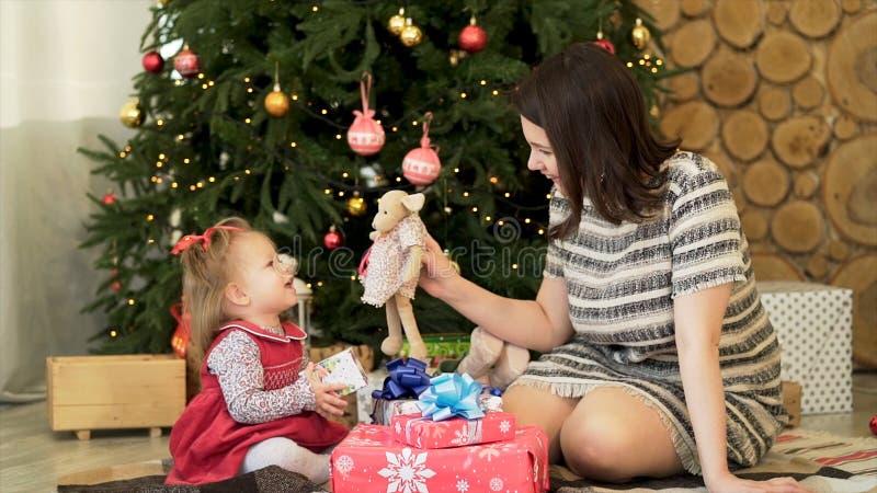 Hija feliz de la familia, de la madre y del niño cerca del árbol de navidad adornado con los regalos que juegan con los juguetes  fotos de archivo