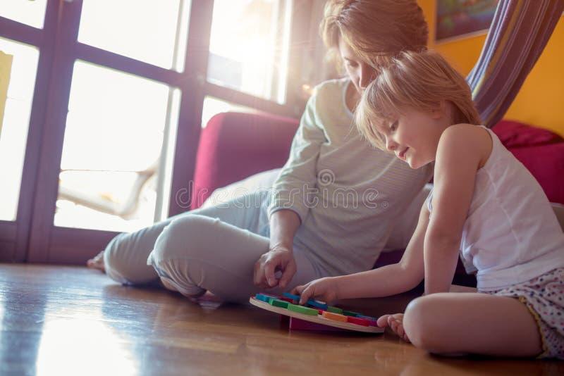 Hija feliz de la madre y de la muchacha que juega en piso de madera de la sala de estar Padres relajados felices que disfrutan de imagenes de archivo