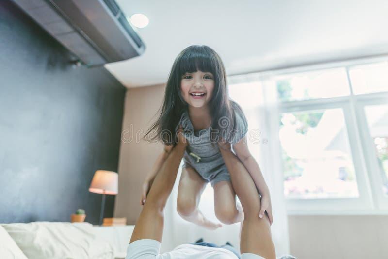 Hija feliz de la niña que juega con el padre mientras que parte posterior del papá del paseo y papá que mienten en la cama en cas fotografía de archivo