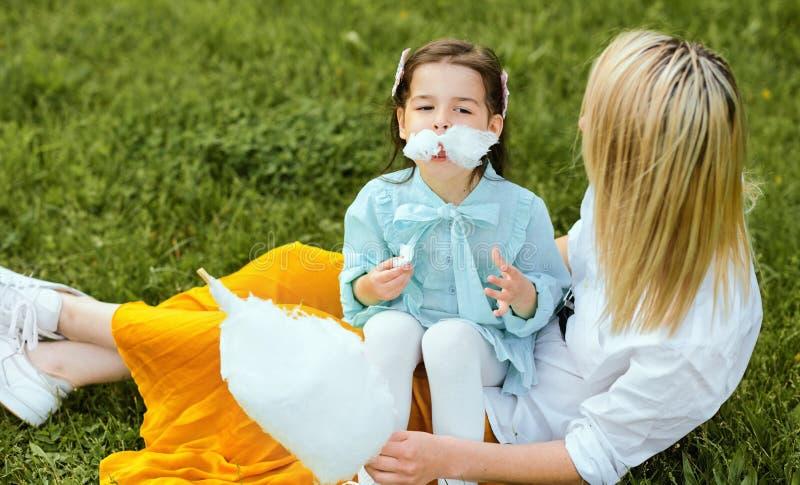 Hija feliz que come el caramelo de algodón con su madre joven en el parque que se sienta en la hierba imagen de archivo libre de regalías